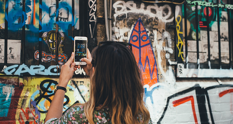 A picture of a woman taking a photo of a graffiti, with her smartphone, on a town house's wall.