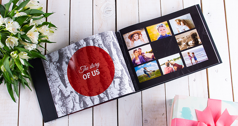 A picture of an open photo book with photos of a little girl and boy – a gift on the right side and white flowers bouquet on the left side of it.