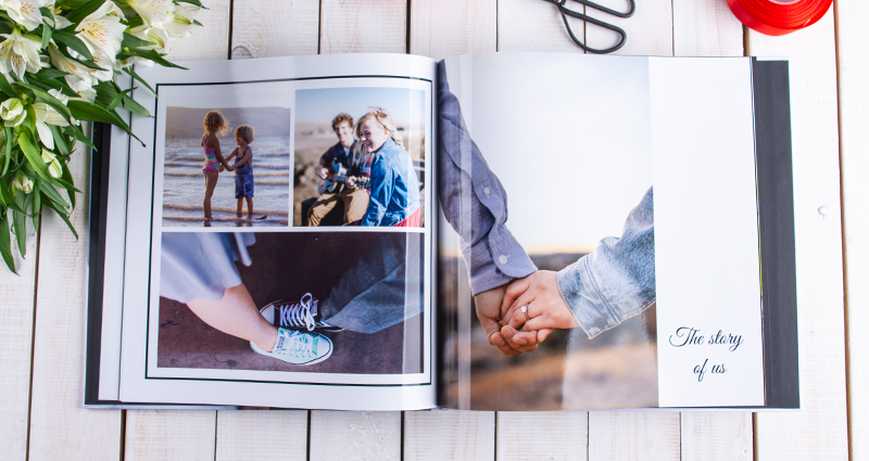 A picture of an open square photo book with pictures of a couple starting from their childhood till present. A photo book on a bright wooden background, red ribbon and scissors above that. White flowers bouquet next to it.