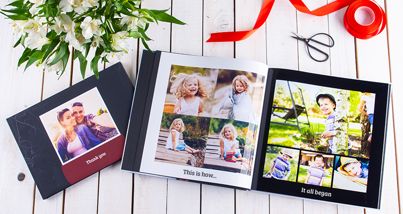 A picture of two photo books – one of the albums with the pictures of a couple and 'Thank you' caption is closed, an open photo book next to it (on the left side page photos from girl's childhood and boy's childhood on the right). Red ribbon and scissors above the open album. White flowers bouquet in the upper left corner.