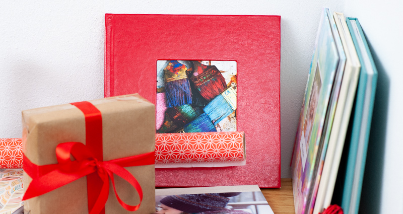 A shelf with different photo book kinds and formats; a gift wrapped with grey paper and a red bow next to it.