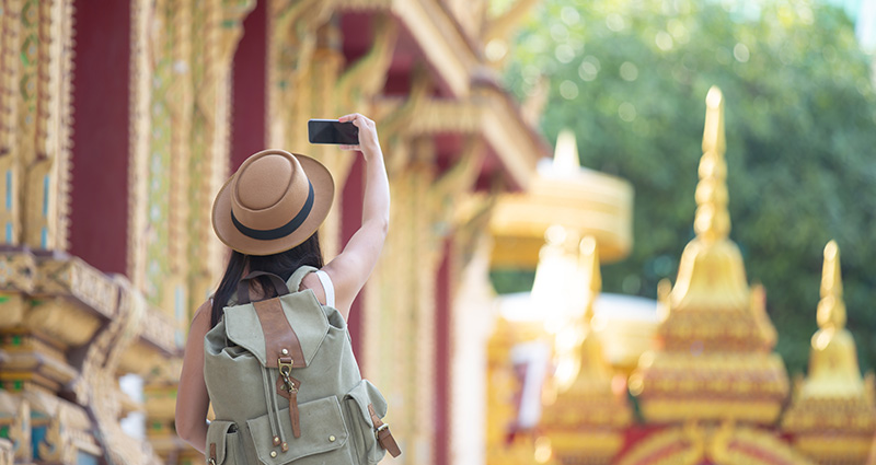 A tourist with a backpack on a holiday in Asia, taking a photo with her smartphone