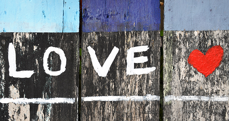 A word LOVE written with white paint on black and grey wooden planks, a red heard next to it; planks painted with blue paint in the upper part