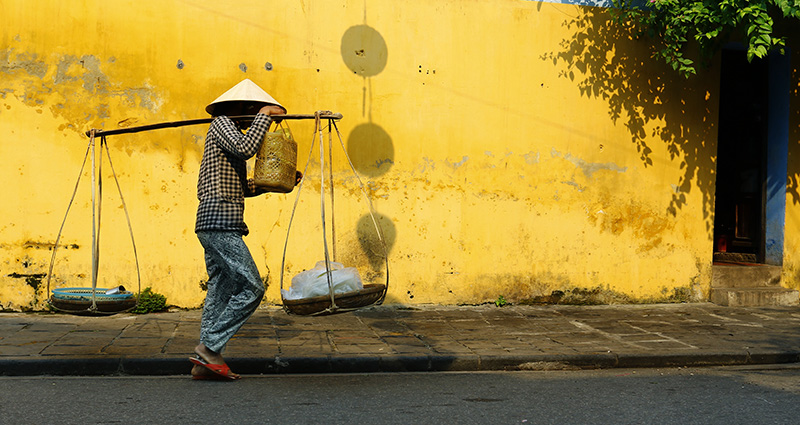 A working man wearing a traditional Vietnamese hat.