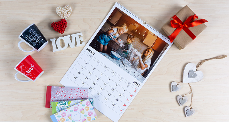 A4 photo calendar with a photo of a family playing together in a kitchen; 3 sharebooks, 2 mugs, a gift wrapped with a red bow and decorative hearts next to it.