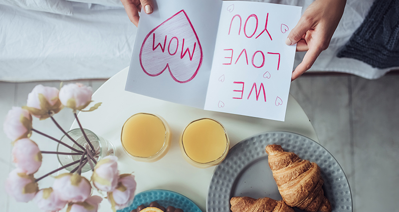"Aerial view – a close up on a card with the ""WE LOVE YOU MOM"" caption. Nearby a bouquet of light flowers, two glasses of orange juice and two croissants."
