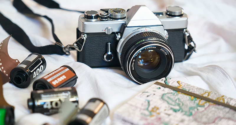 An analogue camera placed next to spare films and a notepad with travelling tips