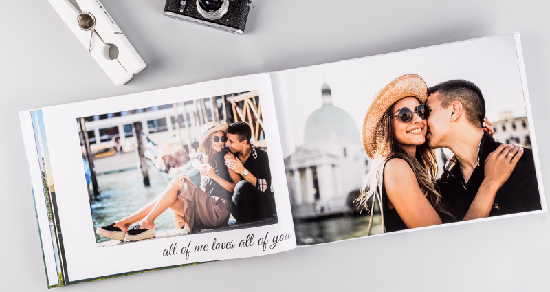 An open photo book A3 landscape, with pictures of a couple in love, lying next to a big paper clip and a camera