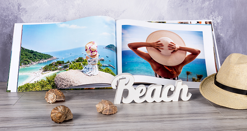 "An open photo book A3, landscape with pictures of a woman by the sea , lying next to some shells, a hat and wooden letters ""Beach"""