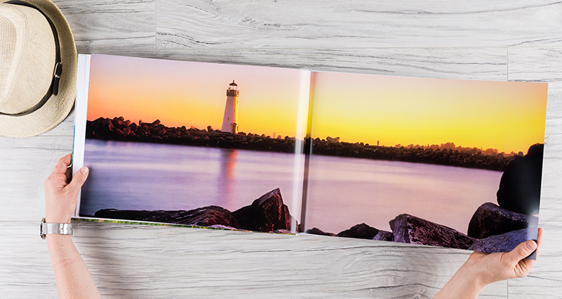 An open photo book A3, with a 2-page landscape picture of the seaside, a lighthouse in the background, lying on the desk next to a hat
