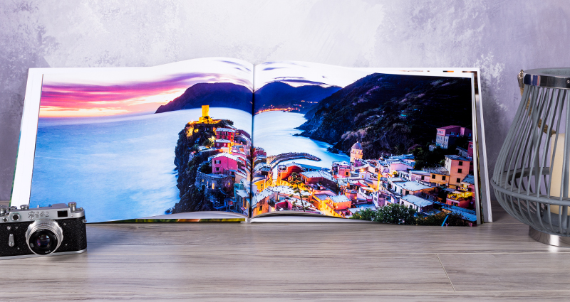 An open photo book A3, with a picture of a seaside resort next to a lantern and a camera, lying on the desk