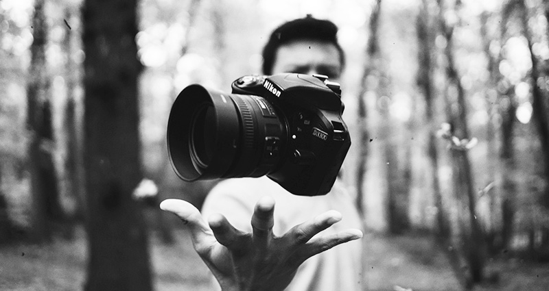 Black and white photograph showing a man in the woods throwing a camera up