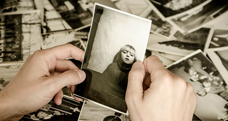 Black and white photographs on the desk; focus on man hands holding a photo of a girl