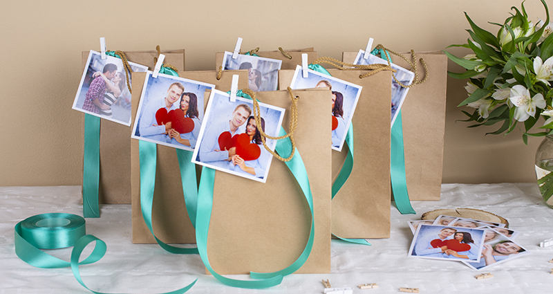 Paper bags decorated with turquoise ribbon and insta photos of a couple attached with a tiny wooden clips. Prints, scissors, spool of ribbon and a white flowers bouquet in a vase. A composition on a white tablecloth.