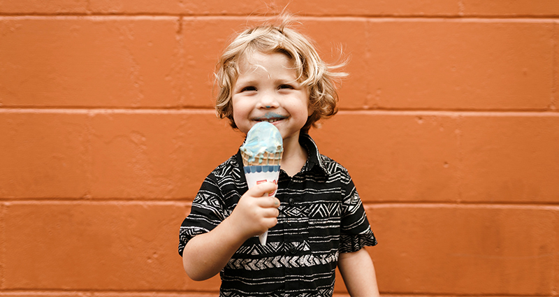 Boy eating ice-creams in the central part of the frame