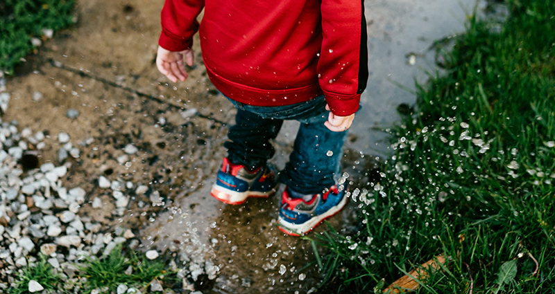 Boy jumping in a puddle