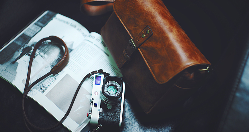 Brown leather bag, a newspaper and a camera in a black armchair