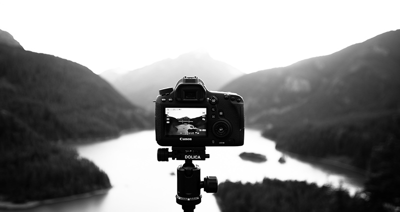 Camera tripod, lake and mountains in the background – black & white photograph