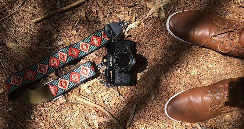 Camera with a handmade strap lying on the ground; focus on brown men's shoes; a picture taken from above