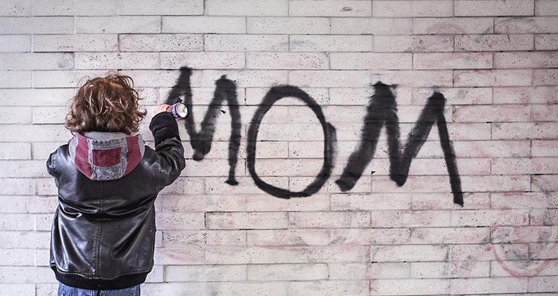 "Child spray painting a word ""MOM"" on the wall"