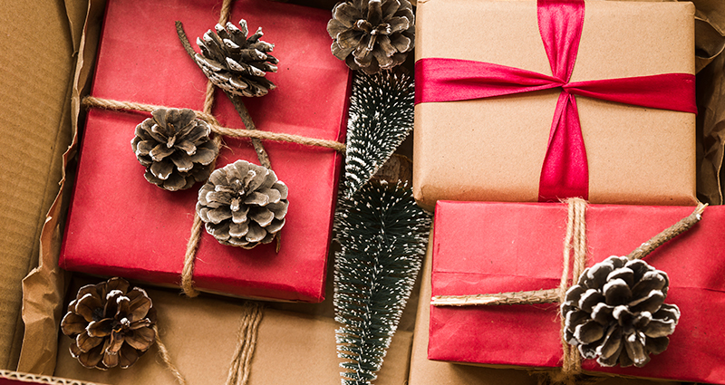 Christmas gifts wrapped in grey and red paper tied with a string, cones next to them.