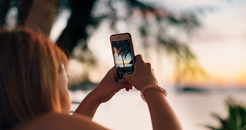 Close up on a woman taking a photo of a palm tree with her smartphone. Sea and sun are in the background.