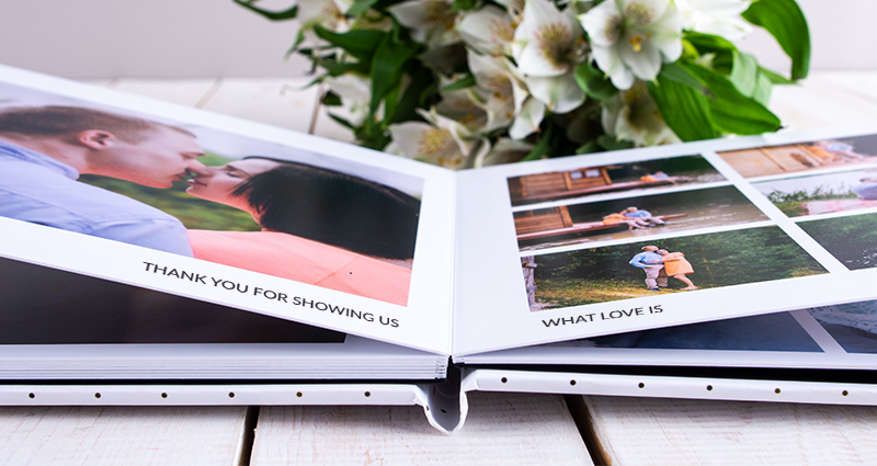 Close up on an open Luxury Album with photos of a couple. White flowers bouquet in the background.