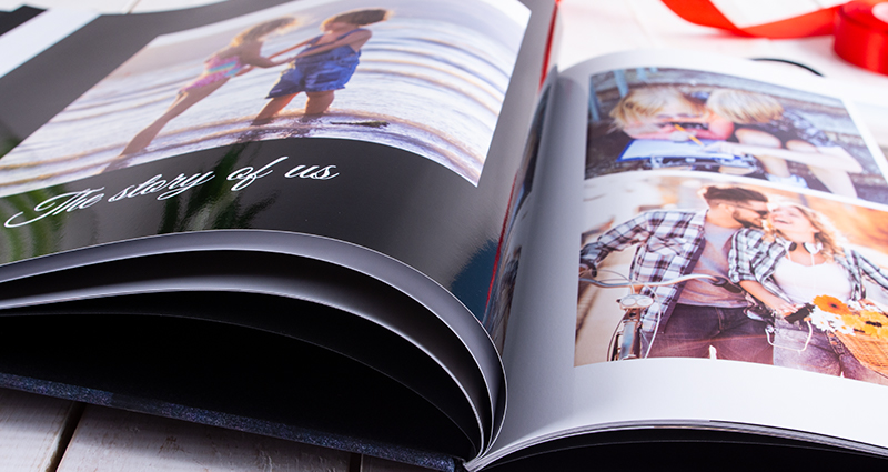 Close up on an open Starbook with photos of a couple starting from their childhood till present.