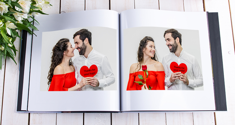 Close up on an open photo book (Starbook) with photos of a couple holding photo prints with captions. White flowers bouquet on the left side and a colourful gift in the upper right corner.
