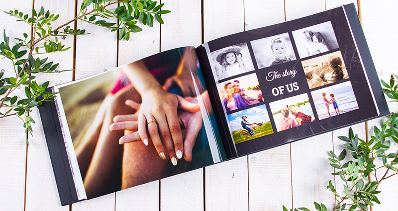 Close up on an open photo book – photo of couple's hands (engagement ring on woman's ring finger) on the left side, a collage on the other page. A photo book on a bright wooden background decorated with green branches.