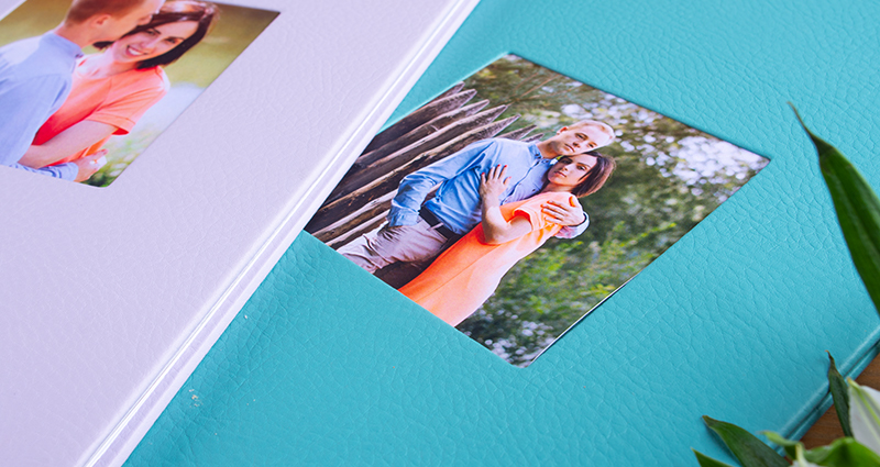 Close up on two Photo Books Exclusive with eco leather cover and pictures of a couple in photo slots, delicate flowers next to it.