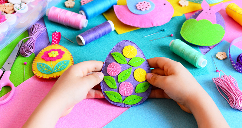 Close-up on a child's hands holding a colourful felt Easter egg. Threads and other felt Easer decorations in the background.
