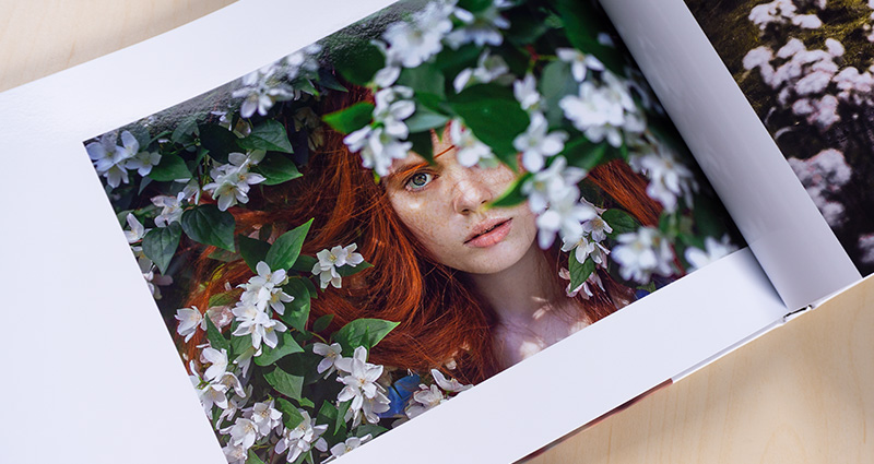 Close-up on a photo from the Starbook with a red-headed woman. White blooming trees in the background.