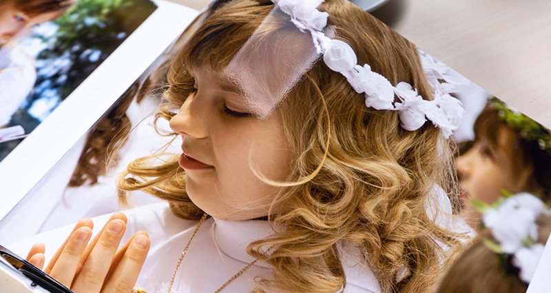 Close-up on a photo of a blonde girl during her First Communion printed in a Starbook.