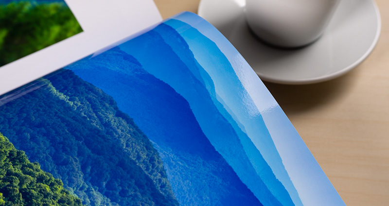 Close-up on a photo of blue sky shades printed in a Starbook. A white cup on a coffee table next to the book.