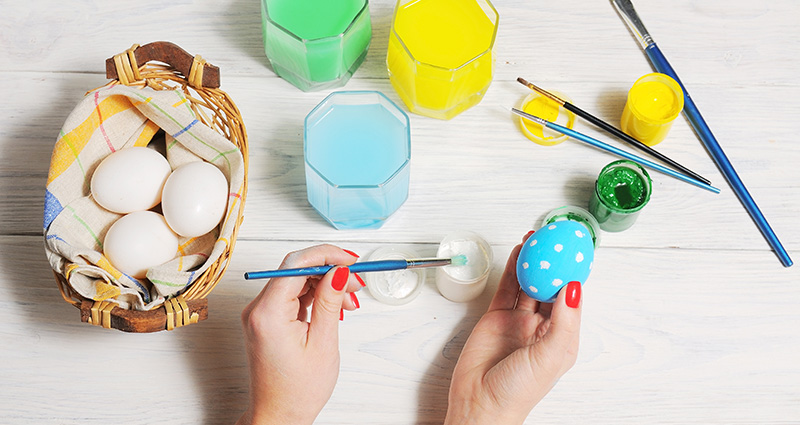 Close-up on a woman's hands painting an Easter egg. Eggs in a basket, colourful paints and brushes laying around.