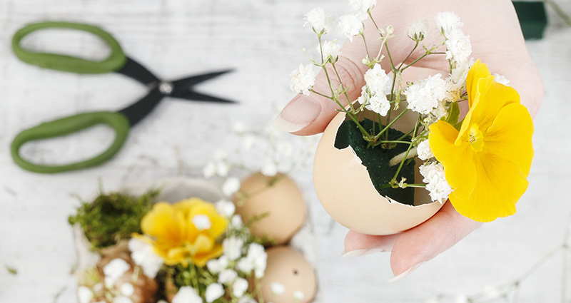 Close-up on woman's hands holding an egg shell with flowers inside. In the background a bright table with scissors and Easter decoration on it.