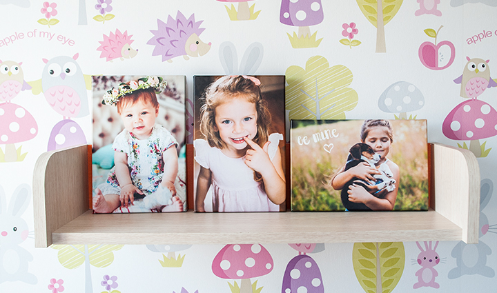 Collection of canvases on a shelf of a girl in various stages of life