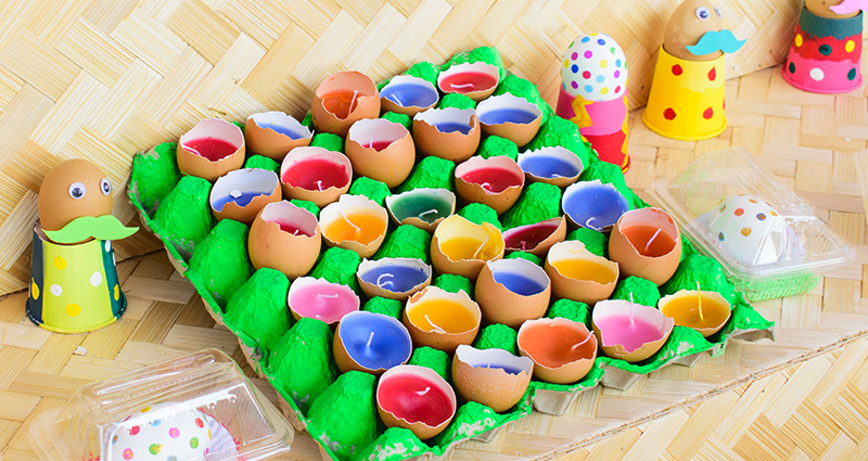 Colourful candles made from blown eggs in a green egg carton.