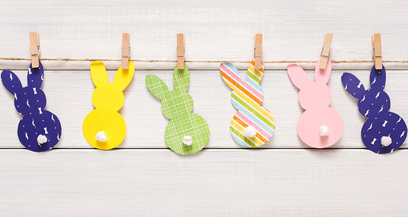 Colourful paper bunnies attached by wooden clothespins to a jute twine hanging close to the wall.