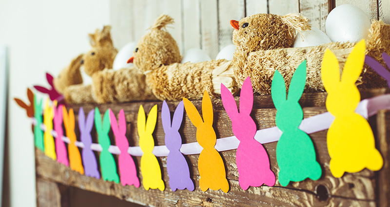 Colourful paper bunnies garland hanging on a wooden beam with Easter decorations on it.