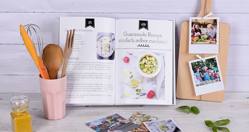 Cookbook lying next to retro prints on a chopping board; cooking utensils in a mug next to photos