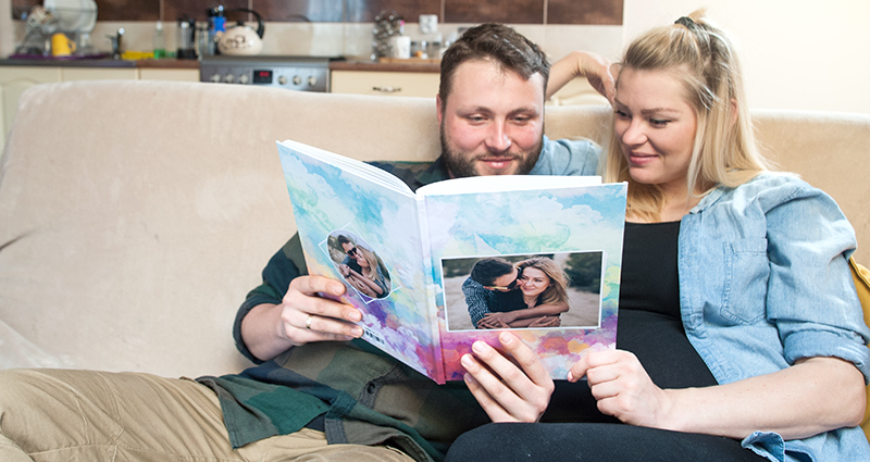 Couple sitting on the couch and reading a wedding guest book