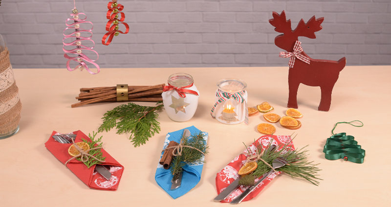 DIY Christmas decorations: decorative cutlery pockets and lanterns made of jars located on a table next to thuja twigs, cinnamon sticks and dried orange slices. There are twigs in a flower pot decorated with linen and Christmas trees made of ribbons.