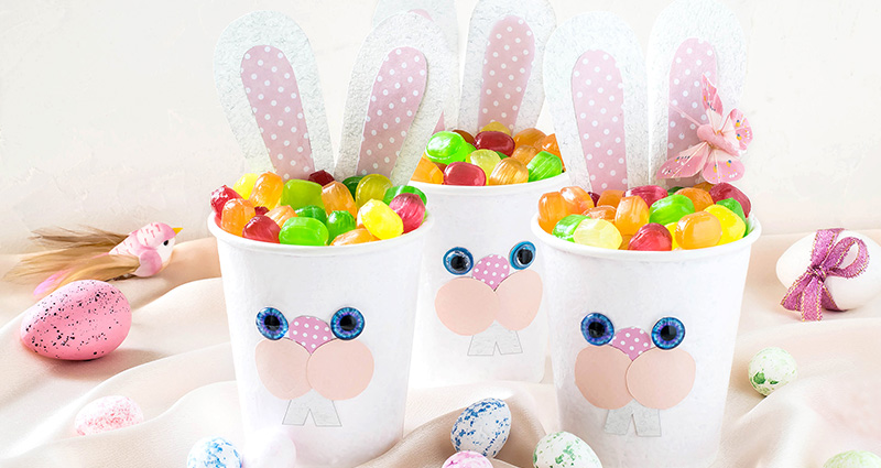 DIY bunnies made from plastic cups full of sweets. Easter eggs all around.