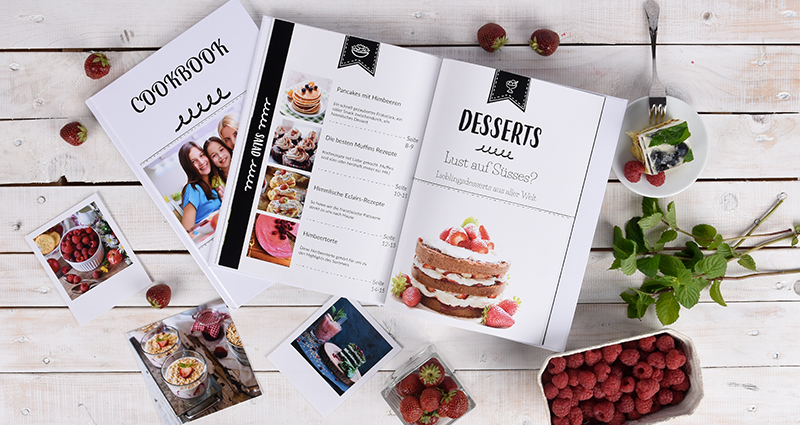 Dessert cookbook lying next to insta photos and retro prints, raspberries, mint and a cookie on a plate