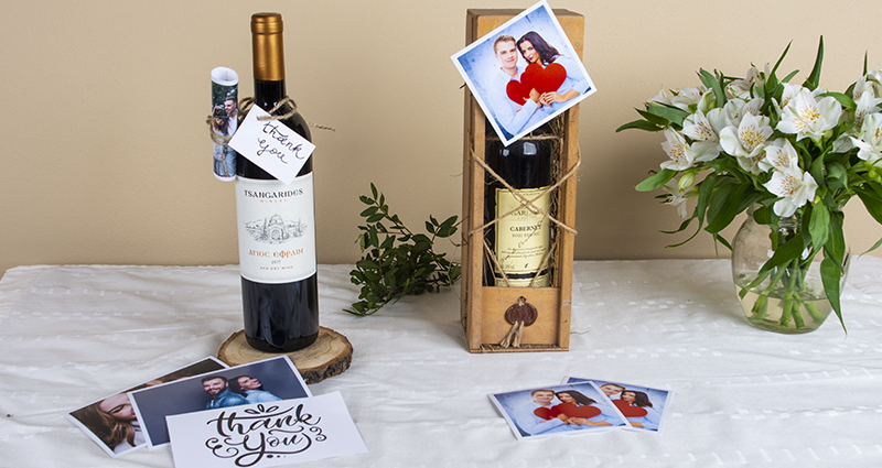 Two wine bottles decorated with prints of a couple and a card saying 'Thank you', prints and insta photos placed next to them and also white flowers bouquet in a vase. A composition on a white tablecloth.