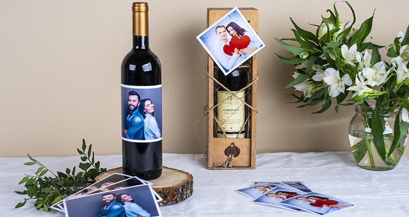 Two wine bottles decorated with prints of a couple, prints, insta photos and whithe flowers bouquet in a vase placed next to them. A composition on a white tablecloth.