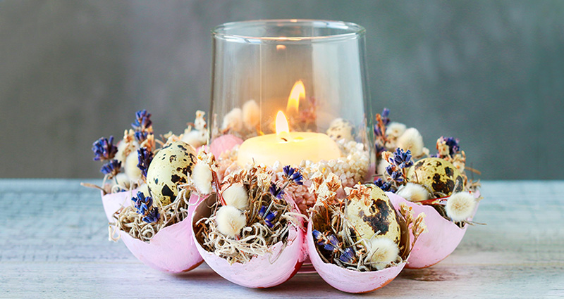 Easter candleholder made of egg shells, moss, catkins and small flowers.