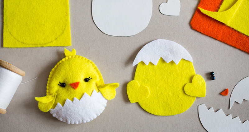 Easter chicken made of felt. Near that threads, paper templates and colourful sheets of felt.